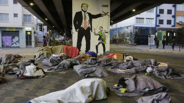 Homeless people sleep under a bridge in front of a mural depicting US President Donald Trump as a puppeteer manipulating Brazil's President Jair Bolsonaro, in downtown Sao Paulo, Brazil.
