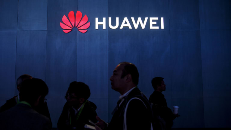 Attendees walk past signage displayed outside the Huawei booth at the 2019 Consumer Electronics Show.