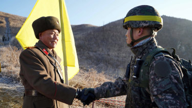 South Korean Army Colonel Yun Myung-shick, right, shakes hands with North Korean Lieutenant Colonel Ri Jong-su before crossing the DMZ line in 2018. They were verifying that each side's old guard posts had been removed.