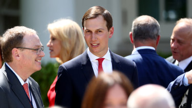 Jared Kushner, senior White House adviser, centre, speaks with attendees after Trump presented the plan believed to be his.