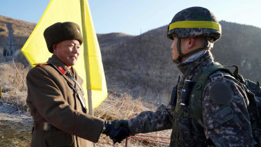South Korean Army Colonel Yun Myung-shick, right, shakes hands with North Korean Lieutenant Colonel Ri Jong-su before crossing the DMZ line this week. They were verifying each side's  old guard posts have been removed.