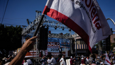 An attendee waves a party flag during a campaign rally with Andres Manuel Lopez Obrador, presidential candidate.