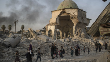 Fleeing civilians walk past the heavily damaged al-Nuri mosque as Iraqi forces continue their advance against Islamic State.