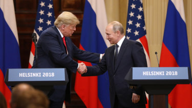US President Donald Trump shakes hands with Russia's President Vladimir Putin during a news conference in Helsinki, Finland, on Monday.