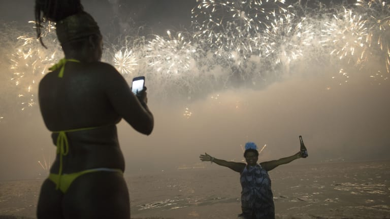 A woman poses for a picture as the fireworks explode over Copacabana Beach.