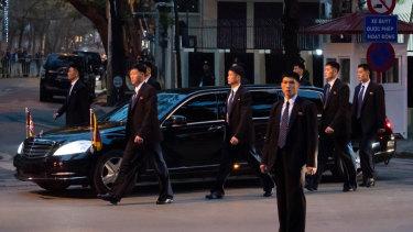 Bodyguard walk alongside a limousine carrying Kim as he arrives in Vietnam.