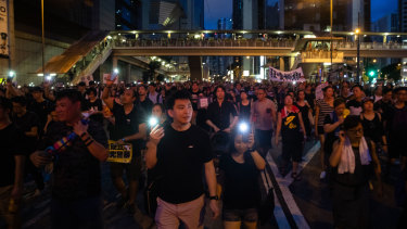 Demonstrators shine smartphone lights as the protest continues into the night.