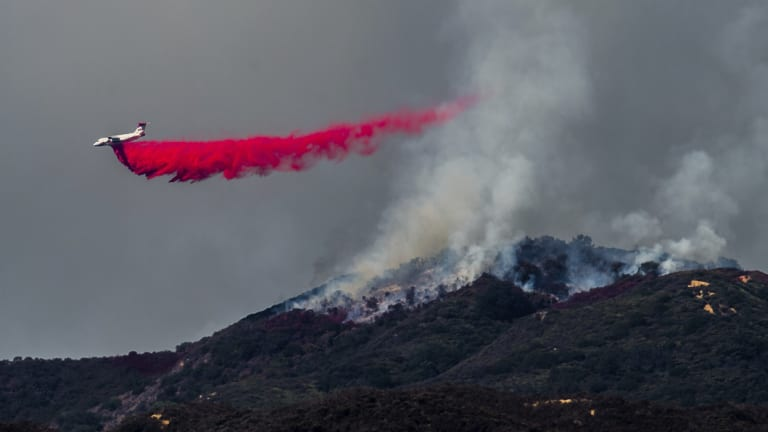 A plane drops fire retardant as firefighters continue to battle a wildfire in the Cleveland National Forest near Corona, California.