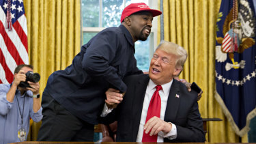 West shakes hands with Trump during a meeting in the Oval Office.