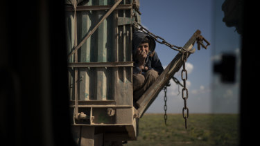 A boy rides in the back of a truck that is part of a convoy evacuating hundreds out of the last territory held by Islamic State militants, in Baghouz, eastern Syria, on Wednesday.
