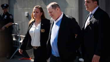 Charged: Harvey Weinstein is escorted in handcuffs out of the New York Police Department.