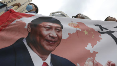 South Korean protesters with an image of Chinese President Xi Jinping stage a rally to denounce the South Korean government's policy on China on Wednesday.