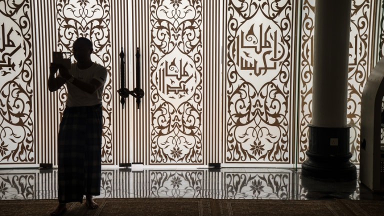 A visitor is silhouetted at the Crystal Mosque in Kuala Terengganu, Terengganu, Malaysia. The country allows child marriages in some cases.