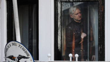Julian Assange readies to open the door to a balcony to speak to media and supporters at the Ecuadorian embassy in London, last year.