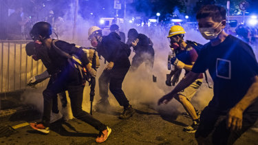 Demonstrators stand in a cloud of tear gas during a protest in the Wong Tai Sin district of Hong Kong, China.