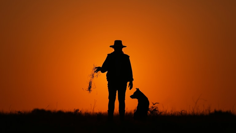 A farmer releasing dead grass while standing next to a dog, silhouetted at sunset on her farm in Wandandian, New South Wales.