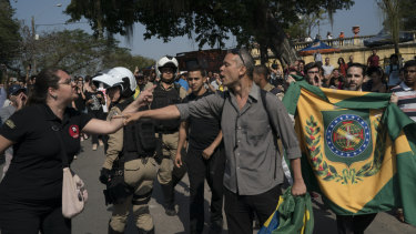 Supporters of Brazil's former monarchy, right, argue with people outside the ruins of National Museum in Rio.