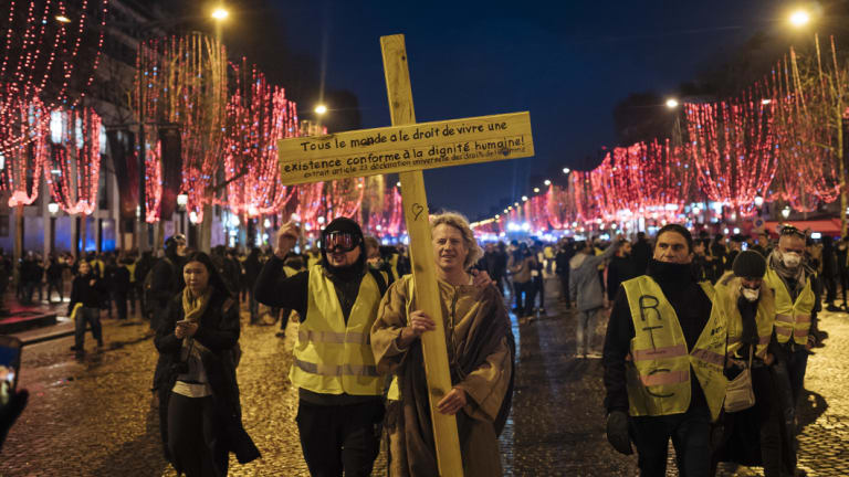 Demonstrators wearing yellow vests hold a cross with an article of the declaration of human rights during a demonstration on the Champs Elysees avenue in Paris on Saturday.