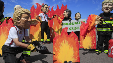 A man wearing a mask President Donald Trump, front left, is joined by other 'world leaders' during a protest ahead of the G-7 summit in Biarritz, France.