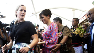 Meghan, Duchess of Sussex is escorted through a crowded market in Suva, Fiji.