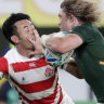 South Africa's Faf de Klerk, right, carries the ball against Japan's Kenki Fukuoka.
