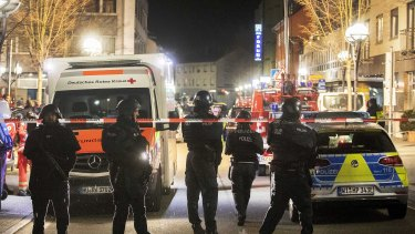 Police stand guard near the scene of a shooting in central Hanau.