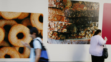 People walk past a doughnut billboard. Behavioural scientists have learnt it is often systems, and environments, that most influence a person's behaviour.