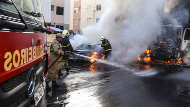 Firefighters put out torched vehicles on a street after attacks in the city of Fortaleza, north-eastern Brazil, on Thursday. Brazil's newly inaugurated government has ordered military police to Ceara state following a wave of attacks on banks, public buildings and infrastructure.