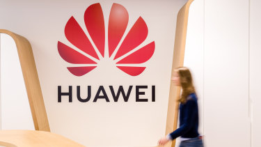An employee walks past a logo in the reception area of the Huawei Cyber Security Transparency Centre in Brussels, Belgium.