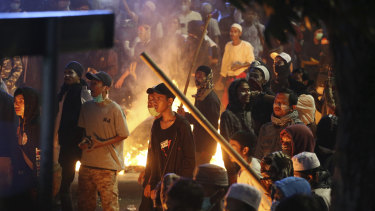 Supporters of the losing presidential candidate stand near a fire during clashes with police on Wednesday night.