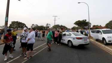 Residents are seen outside an exclusion zone as police detonate an explosive at a Davoren Park property.
