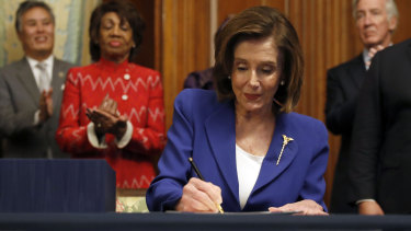 House Speaker Nancy Pelosi signs the Coronavirus Aid, Relief, and Economic Security Act (CARES).