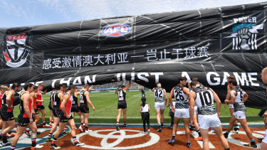St Kilda and Port Adelaide players run through the banner before last year's match in Shanghai.