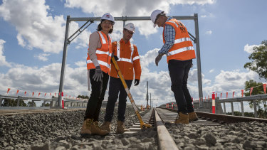 Premier Gladys Berejiklian, site manager Ben Miller and Transport and Infrastructure Minister Andrew Constance at Bella Vista, where the last sleepers for the Metro North West project were locked down.