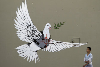 A Palestinian youth walks past the painting of a dove of peace wearing a flak-jacket which is widely attributed to Banksy on a wall in the West Bank town of Bethlehem.