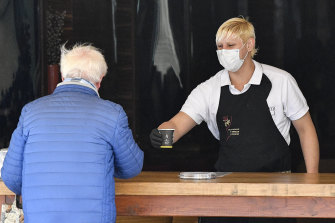 A waiter serves a coffee to go at an ice cream parlour in Gelsenkirchen, Germany.