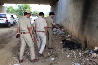 Indian police officers inspect the site where the woman's burned body was found.