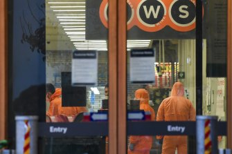 Workers in protective gear prepare to deep clean a Woolworths at Epping Plaza on Tuesday after it was listed as a tier 1 COVID-19 exposure site.