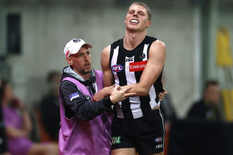 Will Kelly winces in pain after hurting his arm late in the game.