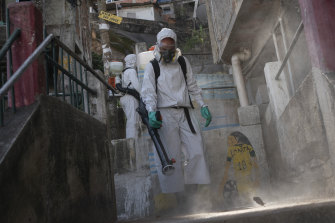 A worker sprays disinfectant in an alley to help contain the spread of coronavirus in Rio de Janeiro, Brazil.
