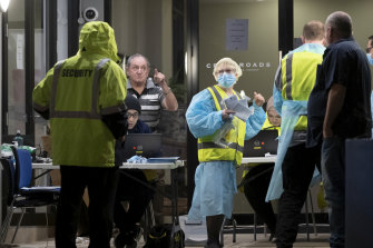 People get checked for coronavirus outside the Crossroads Hotel at Casula on Friday night.