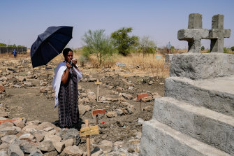 Agere Getnet weeps in front of a tomb containing the remains of her husband, Tebekaw, 37, hisbrother, Alie Abere, and his nephew, Aynew Mulat, among the mass graves at Abune Aregawi Ethiopian Orthodox Church.