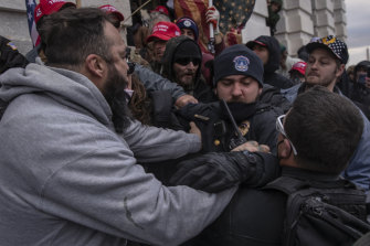 Demonstrators clash with a US Capitol police officer as they attempt to breach the Capital building on January 6.