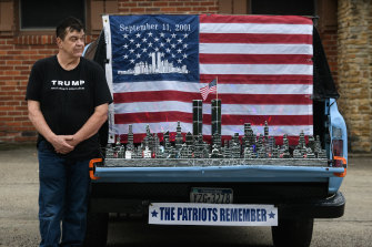 A supporter of President Donald Trump stands next to a 9/11 display on a truck along the Lincoln Highway in Stoystown, Pennsylvania, on Friday.