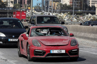 A driver wearing a protective face mask drives a badly damaged Porsche SE luxury automobile in Beirut, Lebanon, on Wednesday.