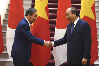 Japan's Prime Minister Yoshihide Suga, left, shakes hands with Vietnam's Prime Minister Nguyen Xuan Phuc after the exchange of documents in Hanoi on Monday.