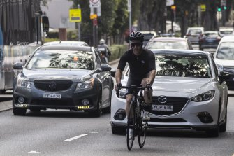 A cyclist weaves through traffic on Cleveland Street.