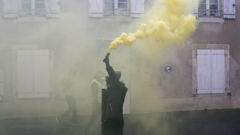 A protester holds a smoke grenade during a demonstration in Bourges, central France, on Saturday.
