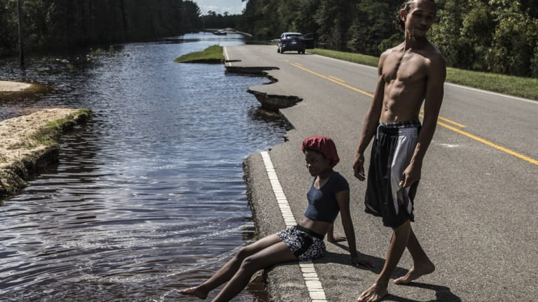A woman sits on a damaged road surrounded by floodwaters in Currie, North Carolina.