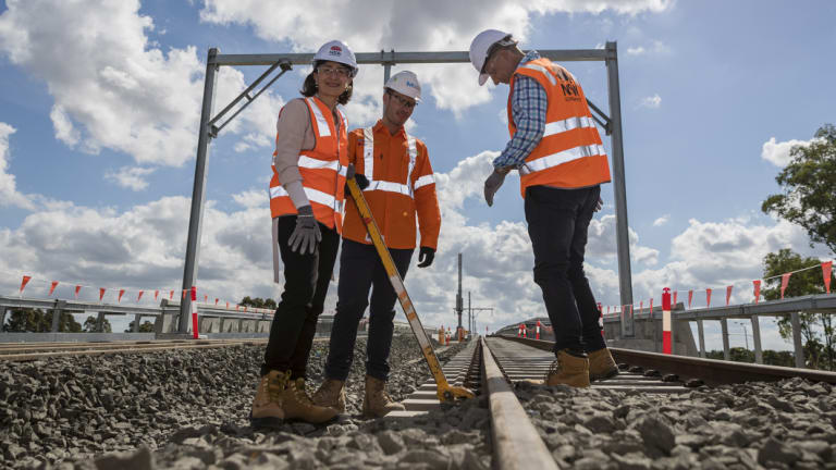Premier Gladys Berejiklian, site manager Ben Miller and Transport and Infrastructure Minister Andrew Constanceat Bella Vista, where the last sleepers for the Metro North West project were locked down.